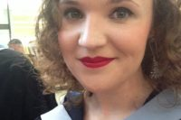 Woman graduating in capping gown, red lipstick, curly hair, gray eyes