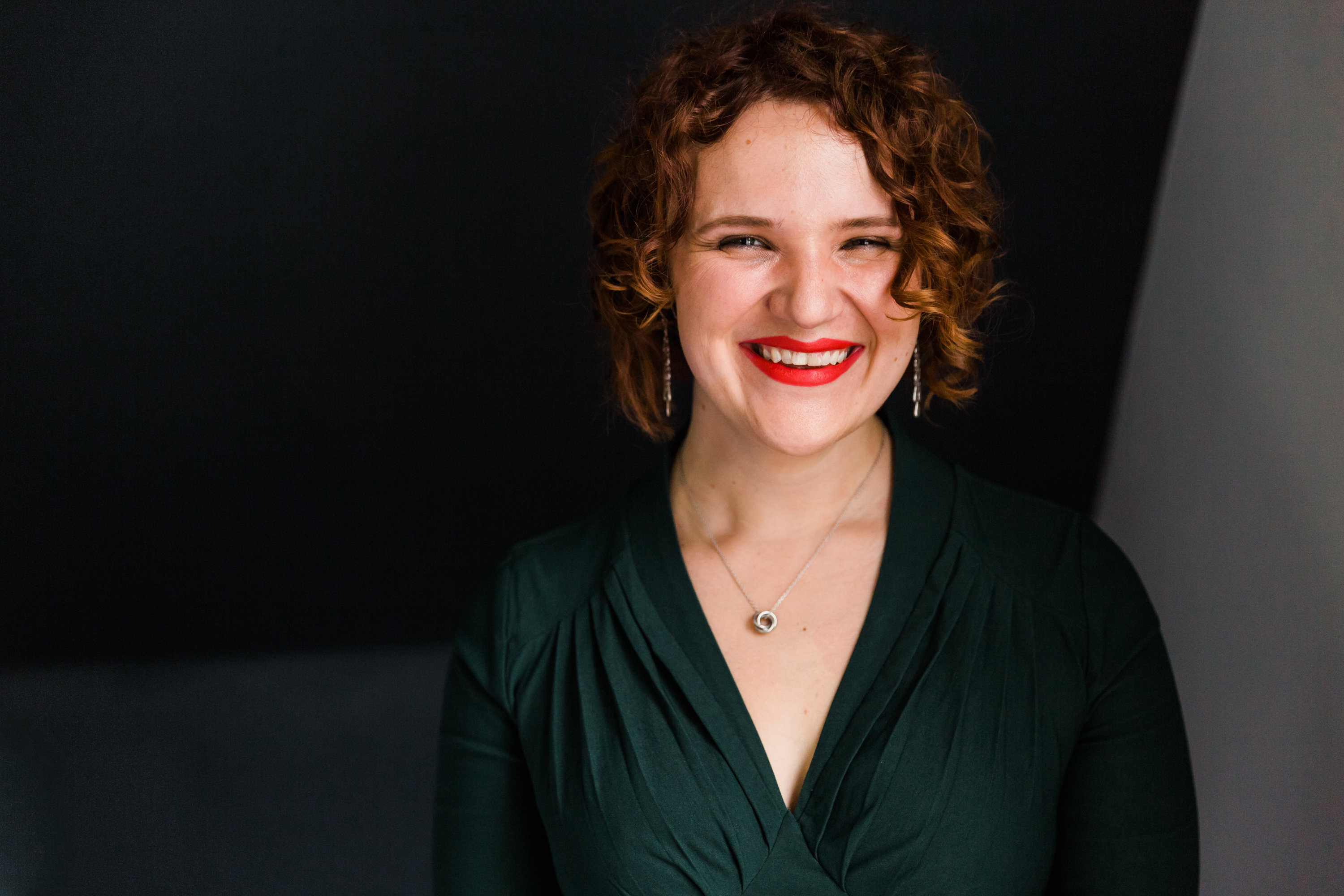 S.A. Borders-Shoemaker, author, smiling, red lipstick, red hair, curly hair, green dress, dark background, Stephanie Michelle Photography