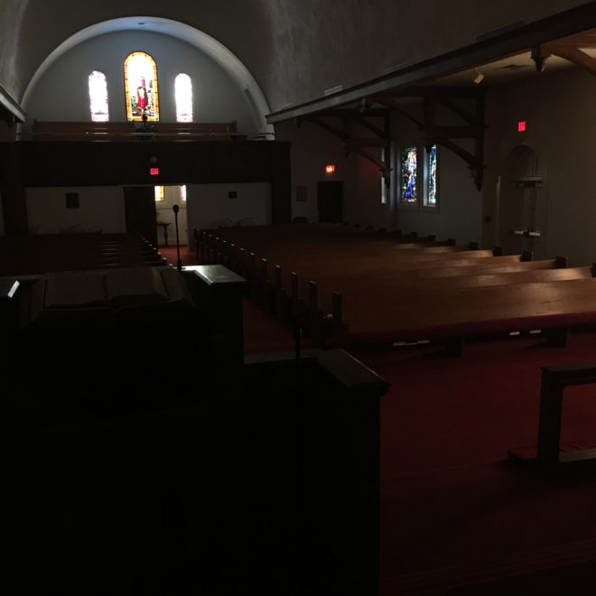 Empty church without lighting, soft glow of stained glass windows