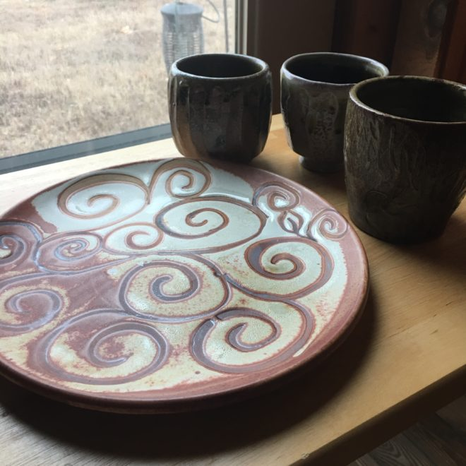 three clay mugs with a clay platter near a window