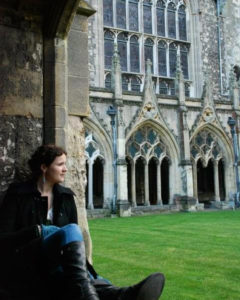 S.A. Borders-Shoemaker sitting on windowsill at Canterbury Cathedral courtyard